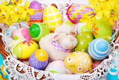 Cesta de Pascua con los huevos y la estatuilla de las ovejas Foto de archivo libre de regalías