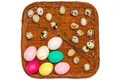 Cesta de Pascua con los huevos y las ramitas coloreados del sauce en el fondo blanco Imagenes de archivo