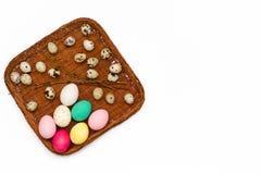 Cesta de Pascua con los huevos y las ramitas coloreados del sauce en el fondo blanco Visión superior Foto de archivo