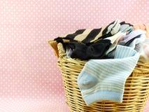 Cesta de peúgas coloridas no fundo cor-de-rosa do às bolinhas Fotos de Stock
