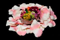 Cesta de plata con las rosas en los pétalos color de rosa de la materia textil Foto de archivo