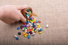 A cesta de seixos coloridos derrama no fundo da lona Foto de Stock Royalty Free
