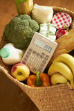 Cesta de tiendas de comestibles con la calculadora Fotografía de archivo libre de regalías