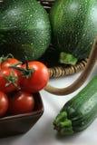 Cesta de tomates y de calabacines orgánicos Imagenes de archivo