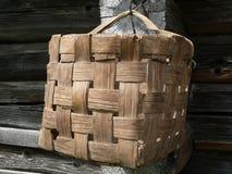 Cesta de uma casca de uma árvore na parede de uma casa de madeira Fotos de Stock Royalty Free