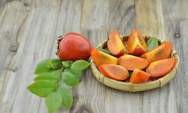 A cesta de vime com caqui e o doce maduros cortou na tabela de madeira Fotos de Stock Royalty Free