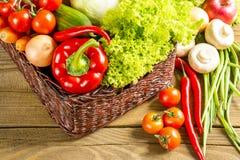 Cesta de vime com frutas e legumes na tabela de madeira Foto de Stock