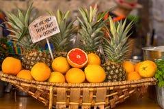 Cesta de vime com laranjas e abacaxis fotografia de stock royalty free