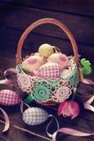 Cesta de vime com os ovos coloridos para easter Fotografia de Stock