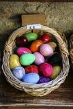 Cesta de vime com os ovos da páscoa de cores diferentes fotos de stock royalty free