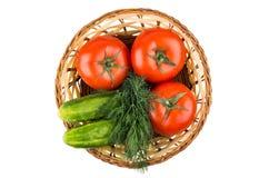 Cesta de vime com os tomates, os pepinos e o aneto isolados no whit Imagem de Stock Royalty Free