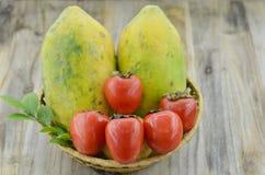 Cesta de vime com papaia doce e caqui maduro na tabela de madeira Fotografia de Stock Royalty Free