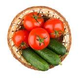 Cesta de vime com tomates frescos e os pepinos isolados no whit Imagem de Stock Royalty Free