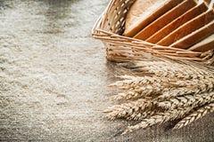 A cesta de vime cortou as orelhas do centeio do pão do brinde em vagabundos de despedida textured Imagens de Stock