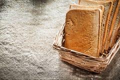 A cesta de vime cortou o pão no fundo de despedida do vintage Foto de Stock Royalty Free