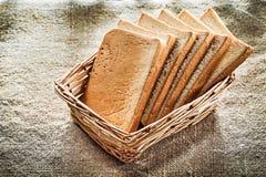 A cesta de vime cortou o pão no fundo de serapilheira do vintage Imagem de Stock Royalty Free