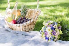 Cesta de vime de frutos frescos e de ramalhete do casamento na grama imagem de stock