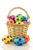 A cesta de vime encheu-se com os ovos de easter coloridos Fotos de Stock