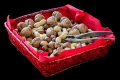 Cesta de vime vermelha com frutos secos, avelã, noz, amêndoa, amendoins e uma quebra-nozes fotos de stock