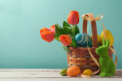 Cesta del día de fiesta de Pascua con los huevos, las flores y el conejito de pascua Fotografía de archivo libre de regalías