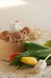 Cesta del día de fiesta de Pascua con los huevos, las flores y el conejito de pascua en de madera rústico Imagen de archivo