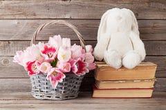 Cesta del ramo de los tulipanes y juguete rosados del conejo Foto de archivo libre de regalías