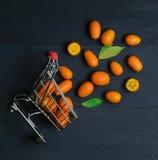 A cesta do carrinho de compras de muitos kumquats dispersa escuro - vista superior alaranjada imagem de stock