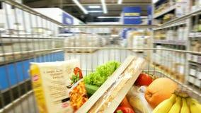 Cesta do carrinho de compras na loja de mantimento do supermercado vídeos de arquivo