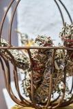 A cesta do metal mantém varas feitos a mão do borrão envolvidas com corda vermelha e branca fotografia de stock