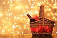 Cesta do presente com a garrafa do vinho contra luzes borradas foto de stock royalty free