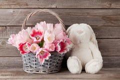 Cesta do ramalhete das tulipas e brinquedo cor-de-rosa do coelho Fotografia de Stock Royalty Free