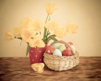 Cesta dos ovos da páscoa e das flores na tabela de madeira Fotos de Stock