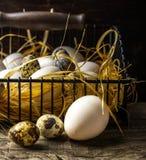 Cesta dos ovos recentemente colocados que encontram-se na palha no Fotografia de Stock Royalty Free