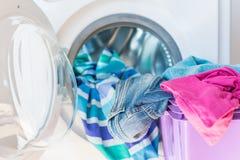 Cesta e máquina de lavar de lavanderia com carga de linho Fotografia de Stock