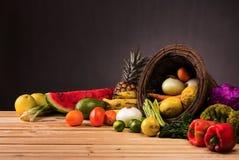 Cesta e tabela completamente de frutas e legumes coloridas Imagens de Stock