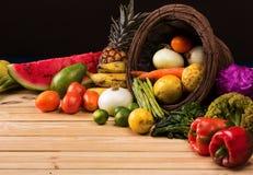 Cesta e tabela completamente de frutas e legumes coloridas Imagem de Stock Royalty Free