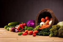 Cesta e tabela completamente de frutas e legumes coloridas Fotos de Stock Royalty Free