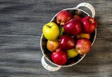 Cesta en manzanas rojas, cesta por completo de las manzanas, imágenes de las manzanas en piso de madera auténtico, Imagen de archivo libre de regalías