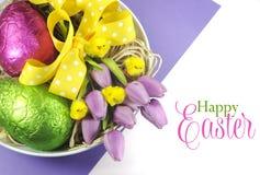 Cesta feliz de Pascua de huevos en embalaje flexible rosados y verdes coloridos y de tulipanes púrpuras rosados con los polluelos