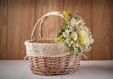 Cesta festiva adornada con las flores en fondo de madera Imagen de archivo libre de regalías