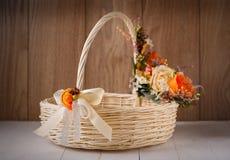 Cesta festiva adornada con las flores en fondo de madera Fotos de archivo libres de regalías