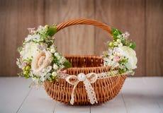 Cesta festiva adornada con las flores en fondo de madera Imágenes de archivo libres de regalías