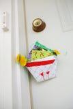 Cesta hecha en casa de flores que cuelgan en una puerta Imagen de archivo libre de regalías