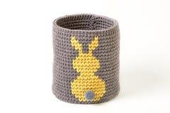 Cesta hecha punto con el conejo amarillo en el fondo blanco Fotos de archivo libres de regalías