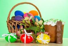 Cesta, huevos, una torta de Pascua, conejo, alstromeria Imagenes de archivo