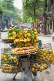 Cesta llena de fruta anaranjada en la bici del vendedor en la calle de Hanoi, Vietnam Imagen de archivo libre de regalías