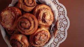 Cesta llena de rollos de pan dulces con las semillas del canela y de sésamo metrajes