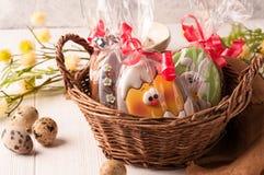 Cesta marrón de mimbre con las galletas envueltas de pascua cerca de los huevos de codornices y de la rama floreciente foto de archivo