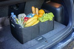 Cesta negra del bolso por completo de productos en el tronco de coche fotografía de archivo libre de regalías