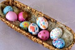 Cesta oval por completo de huevos de Pascua brillantemente coloreados fotos de archivo libres de regalías